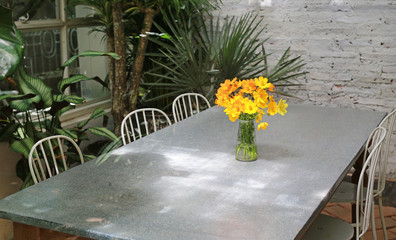 Table and chair with yellow cosmos flowers in vase on the table. Garden decoration.