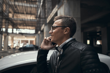 Close-up. A young handsome man talking on the phone. He smiles. Standing at the car parking