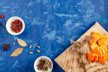pumpkin cut on a blue background is lying along with the seasonings, the process