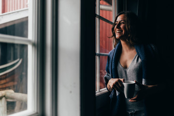 Woman with mug near window