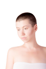 Portrait of sad woman with bald haircut with bare shoulders on isolated white background