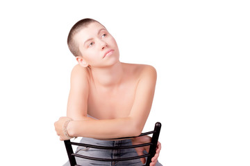 Portrait of woman with bald haircut sitting on chair with bare shoulders on isolated white background