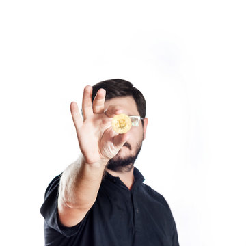 Portrait of 30 years old caucasian man holds Model of Gold Bitcoin