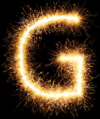Sparkler firework light alphabet G isolated on black