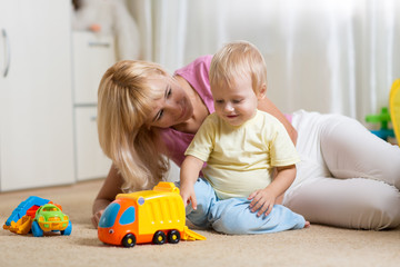 Moher and her toddler son plays with car toys in his cosy childrem room