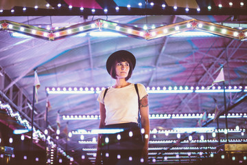 Stylish woman posing in illuminated night park