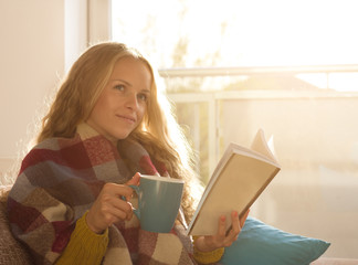 Girl reading book and drinking tea at home