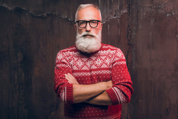 Beautiful senior bearded man in Christmas sweater. Santa Claus wishes Merry Christmas