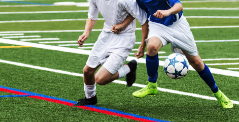 Two soccer players fight for the ball