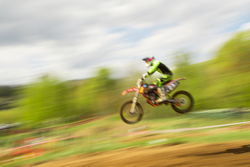 Biker on motocross jump in motion
