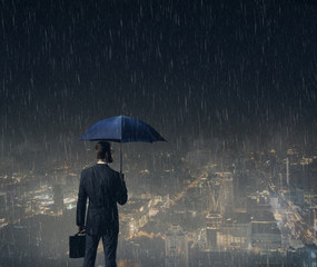Businessman with umbrella standing over night city background.  Business, crisis, failure, concept.