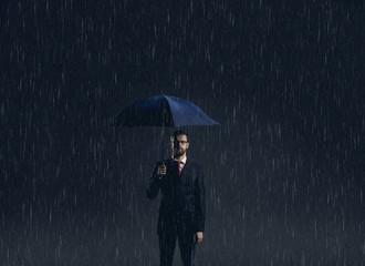 Businessman with umbrella standing under the rain. Dark, dramatic background. Business, failure, crisis, concept.