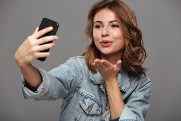 Close-up photo of young attractive woman sending air kiss while taking selfie on smartphone