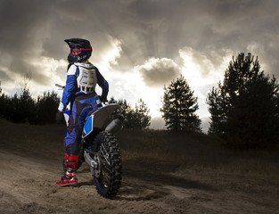 Stores à enrouleur Motorise A portrait of motocross rider sitting on the bike and looking back to the camera on the sunset