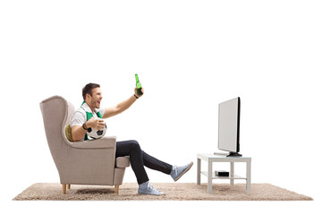 Excited soccer fan watching football on television and having a beer