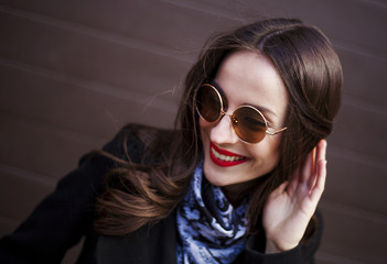 young gorgeous woman in stylish sunglasses posing against brown wall background