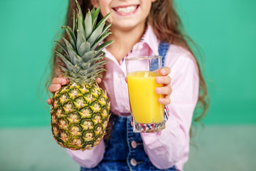 Juice in a glass and pineapple. The concept of a healthy lifestyle, food, childhood, vitamins, vegetarianism.