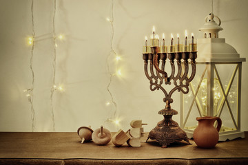 Low key image of jewish holiday Hanukkah background with traditional spinnig top, menorah (traditional candelabra)