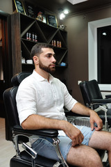 A man sitting in an armchair in a barber shop will shave his beard