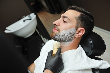 Hairdresser applies a foam brush on his face to shave his beard