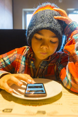 Child using a smart phone in a restaurant