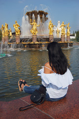 tourists in Moscow: a woman looks at the fountain of peoples' friendship at VDNKh