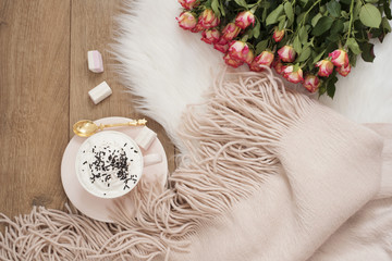 Cozy Winter Mornings. Cappuccino, bouquet of roses and a warm scarf on a white fur carpet on the floor