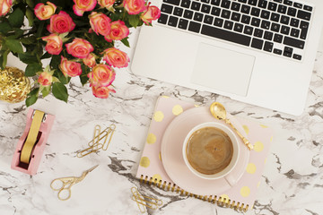 Feminine workplace concept. Freelance workspace in flat lay style with laptop, coffee, flowers, golden pineapple, notebook and paper clips on white marble background. Top view, bright, pink and gold