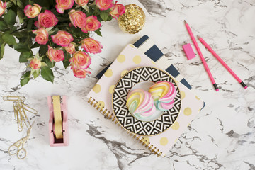Feminine workplace concept. Freelance workspace in flat lay style with sweets, flowers, notebooks on white marble background. Top view, bright, pink, stripe and gold