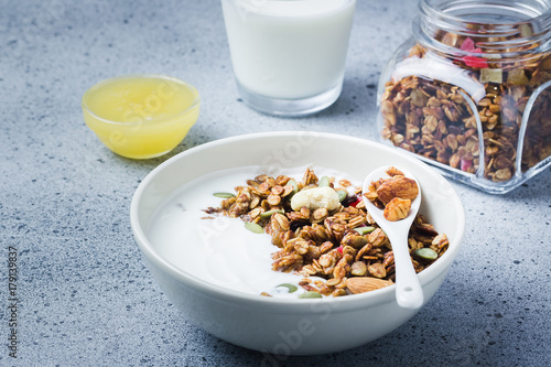 Homemade coconut oil honey almond granola and yogurt on dark