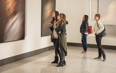 Four girl friends looking at modern painting in art gallery