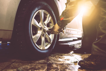 Mechanic hands with wrench changes wheel on car with special equipment in car repair service shop