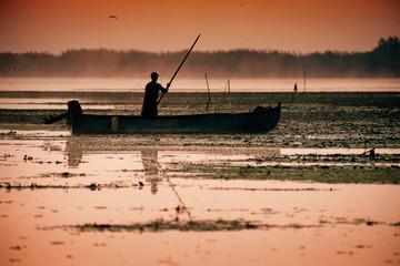 Traditional fisherman catching fish at sunrise in Delta Dunarii, Romania