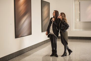 Two girl friends looking at modern painting in art gallery