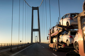 Brand-new cars on a car transport truck. Car transporter trailer on the long bridge in the evening