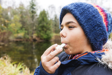 Child using an inhaler or puffer outside in the cold