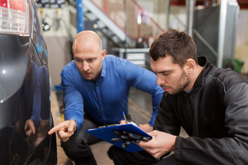 auto mechanic and customer looking at car