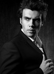 Confident ambitious handsome man with strained look posing in fashion suit and white style shirt on dark shadow background. Closeup black and white portrait
