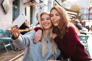 Two happy smiling girls taking a selfie