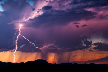 Lightning illuminates a thunderstorm at sunset