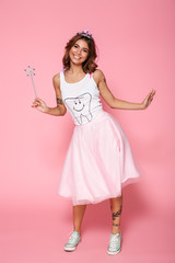 Full length portrait of smiling young brunette woman dressed like princess holding magic wand, looking at camera