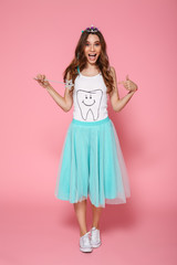 Full length portrait of overjoyed pretty brunette woman dressed like princess pointing with finger, looking at camera