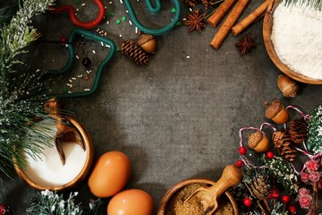 Christmas baking Ingredients  -eggs,flour,cutters,flour and spices on festive holiday background