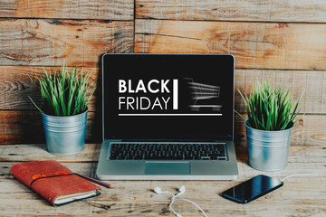 Black friday advertisement in a laptop computer screen placed on a wooden workplace.