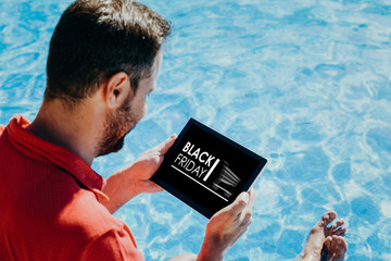 Man shopping by internet Black Friday special offers with an electronic tablet at the swimming pool.