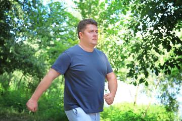 Overweight man running in green park