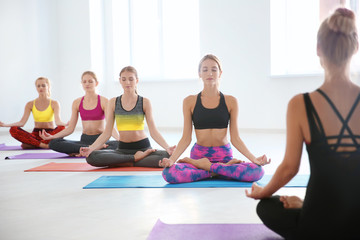 Group of young women practicing yoga in light room