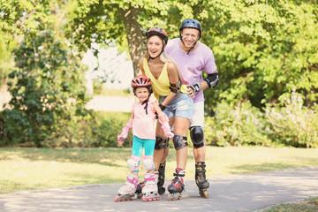 Family on roller skates in summer park