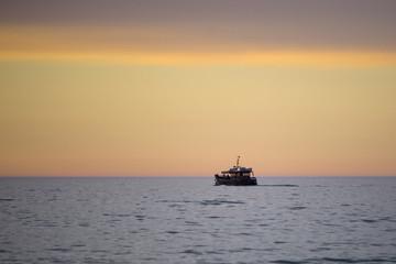 Statek na tle zachodu słońca na plaży nad morzem.