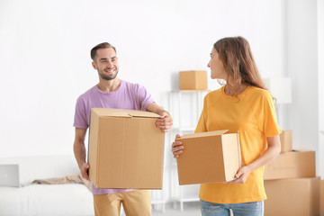 Young couple with moving boxes at new home